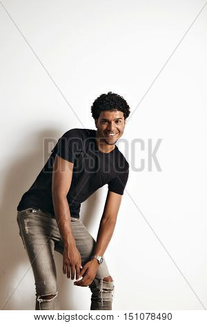 Moving playful athletic black model with an afro wearing a blank black t-shirt and grey skinny jeans against white wall background