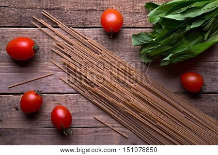Dry whole wheat spaghetti with fresh leaves of ramson and red cherry tomatoes on wood table