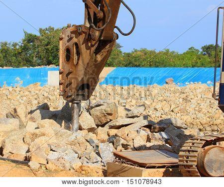 power shovel hammering splitter cylinder on rock to break it up, near Songkhla, Thailand