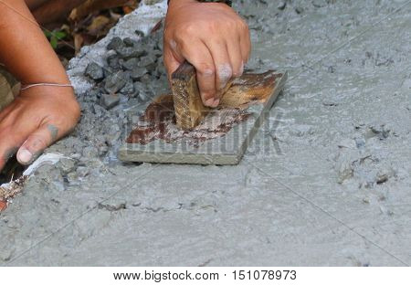 two man's hands seen hand troweling wet concrete onto driveway, using handmade wooden trowel, near Songkhla, Thailand