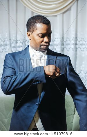 Handsome man african American groom in elegant suit coat with white tie and handkerchief pocket square for wedding ceremony