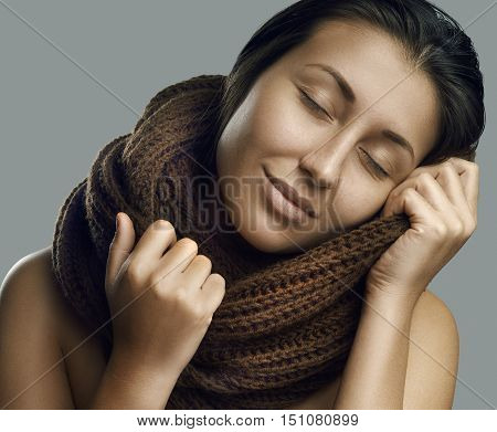 Fashion beautiful woman in warm knitted scarf. Autumn color. Studio shoot