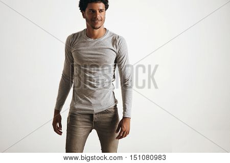 Sexy fitted latino male walking wears blank unlabeled grey logsleeve and stressed jeans, isolated on white