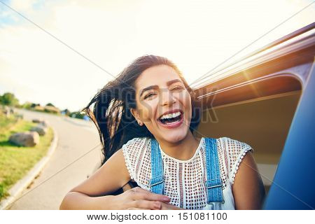 Cheerful young woman with brown hair in car as it speeds down winding road