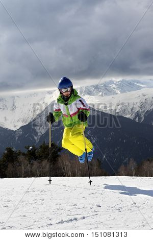 Young skier jump with ski poles in sun winter mountains and cloudy gray sky. Caucasus Mountains. Hatsvali Svaneti region of Georgia.