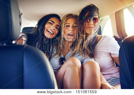 Three happy young women traveling on vacation together sitting arm in arm in a car laughing and smiling viewed from the front seat