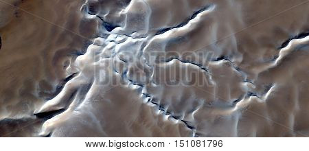 snow on the tops of dunes seen from the air, mirage in the Sahara desert, abstract surreal landscapes, backgrounds brown and tan, white starry branches, hazy fantastic view from the imagination,
