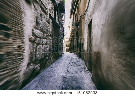 Light at the end of the narrow streets between the old stone houses. Blur motion.