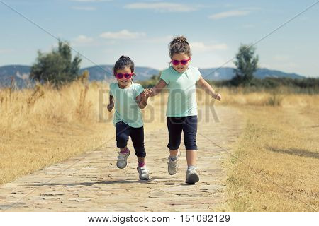 Portrait of little girls in similar wear jumping holding hand in hand along stone path in park