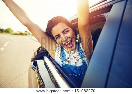 Cheering laughing young teenage girl hanging out of an open car window as it drives along a rural road with her arms extended in the bright early morning sun