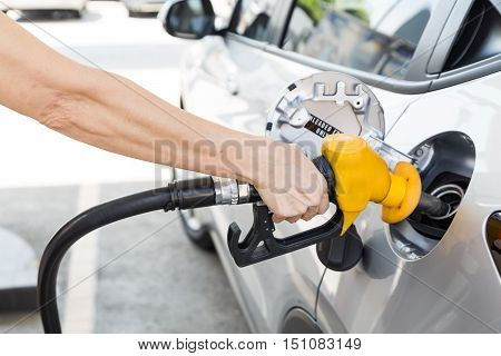 Person Holding Yellow Nozzle Filling Petrol Into Car