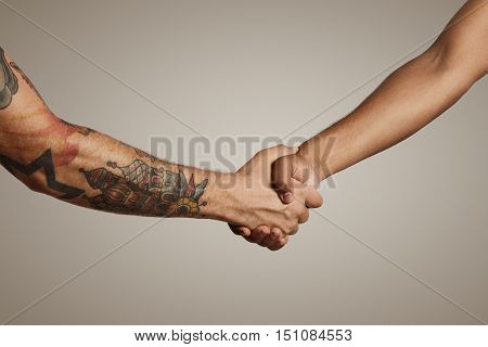 Firm handshake of two muscular men's hands, one with tattoos one without, isolated on white