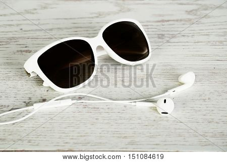 White Female Sunglasses And  Headphones On A Light Wooden Background