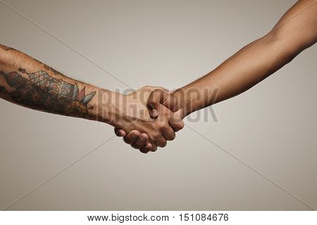Two hip young men shake hands isolated on white