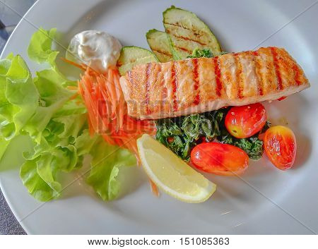 Salmon steaks grill served with salad and grilled vegetables for healthy people on the white dishSoft focused