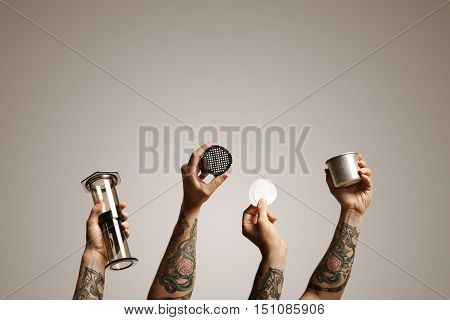 Four shots of hands holding various aeropress parts combined in one image with off white background Alternative coffee brewing commercial