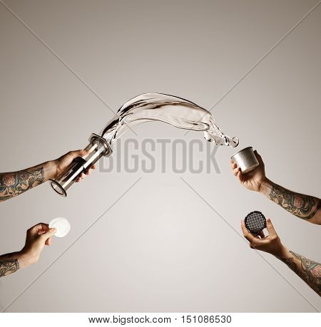 Water flying out of aeropress into steel travel cup with aeropress spares isolated on white Alternative coffee brewing commercial