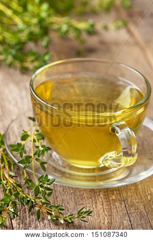 cup of thyme tea fresh thyme on the old wooden background