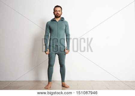 Young fitted bearded male wears thermal base layer suite , standing in front of white wall