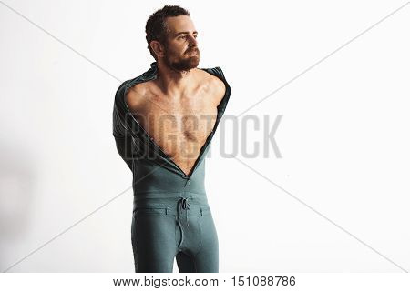 Serious brutal and fitted bearded male athlete dressing off his warm winter snowboarding baselayer thermal suite from merino wool