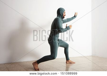 Bearded funny man poses like a ninja wearing his thermal baselayer thermal suite, isolated on white