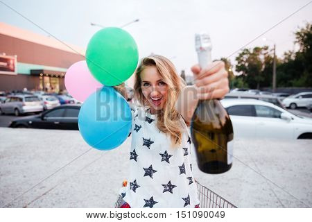 Cheerful young girl holding bottle of champagne and balloons outdoors