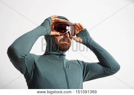 Bearded male athlete in baselayer thermal suite wears snowboarding googles