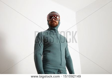 Young fitted bearded male athlete in baselayer thermal suite wears snowboarding googles, looking on side, isolated on white wall