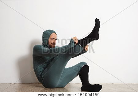 Funny fitted male athlete in winter thermal suite dressing up his long snowboard socks on floor