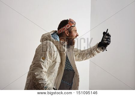 Bearded young man in snowboard jacket and googles on his head screaming into walkie talkie in front of him, isolated on white