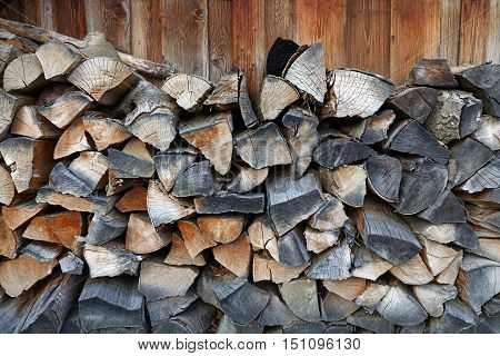 Firewood stock for traditional natural winter fireplace split chop wood fuel arranged in woodpile stack heap close up