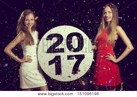 Two beautiful young girls having fun at a New Year's party holding a cardboard circle with the numbers 2017 written on it