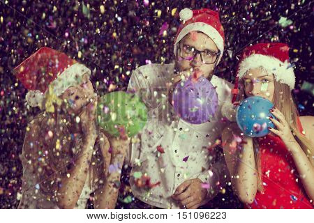 Group of friends having fun at New Year's party wearing Santa's hats and blowing balloons