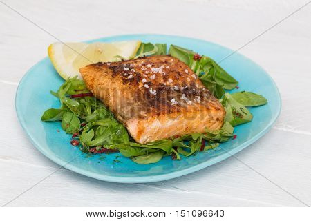 Fried salmon fillet with fleur de sel on mixed salad.
