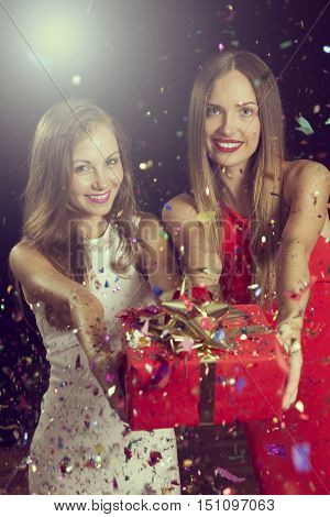 Two attractive young women having fun at a party holding a nicely wrapped gift box and offering it to someone