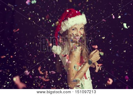 Attractive beautiful woman wearing Santa's hat having fun and dancing at New Year's Eve party