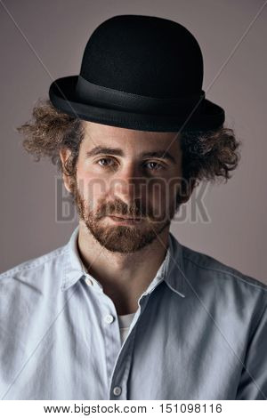 Portrait of a sad looking young bearded jewish man with curly hair wearing a funny black bowler hat and light denim button up t-shirt isolated on light gray.