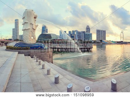 Singapore, Republic of Singapore - May 4, 2016: Singapore central quay at sunrise with Merlion lion fountain on foreground