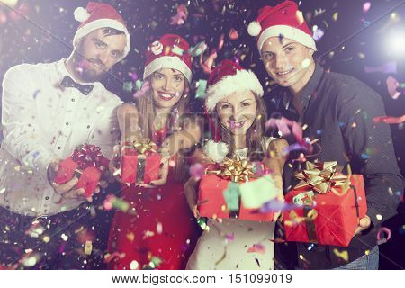 Two couples having fun at New Year's party and holding nicely wrapped present boxes