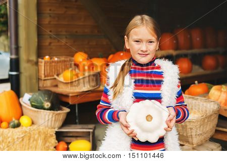 Adorable little girl of 8-9 year old choosing halloween pumpkin on farm market, holding white squash
