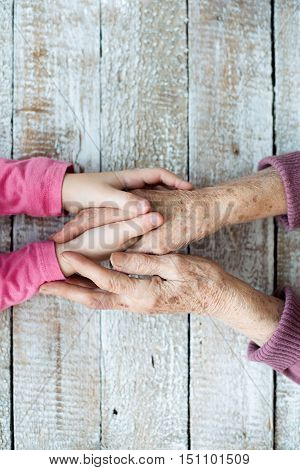 Close up. Unrecognizable grandmother and her granddaughter holding hands. Studio shot on white wooden background. Copy space