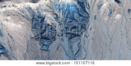 Mirage in the desert simulating a detachment of blue stone forming a large avalanche gullies of the gray mountains of the deserts of Africa,air photography from the African deserts,abstract naturalism