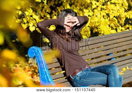 Attractive young woman sitting on brown wooden bench with her hands hide her eyes in a beautiful park. She close her eyes. Golden autumn foliage around. Girl wears blue jeans and turtleneck sweater. Yellow color dominates