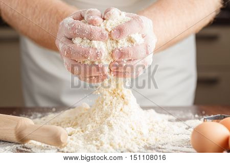 man hands kneading a dough on table