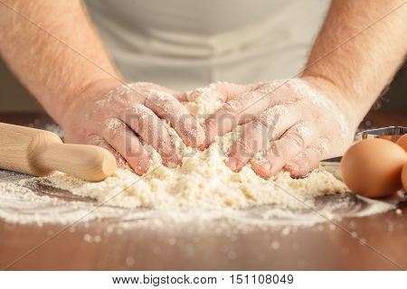 Male Hands kneading a dough on wooden table