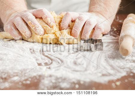 Pair of hands kneading dough on wooden table