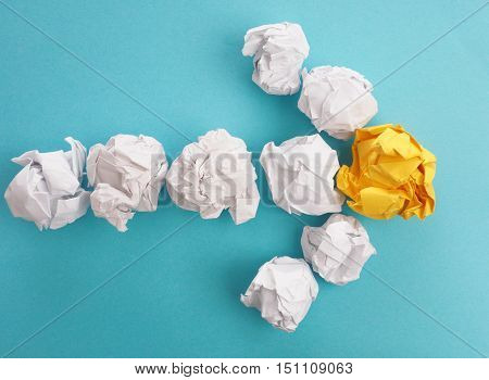 An arrow of crumpled paper on a blue background