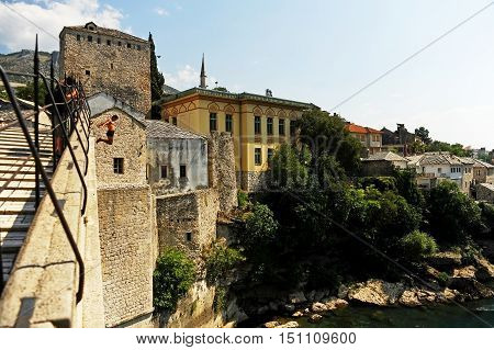 MOSTAR BOSNIA AND HERZEGOVINA - AUGUST 29: Tourists watch a high diver jumping from the old bridge of Mostar into Neretva river on August 29 2015 in Mostar.