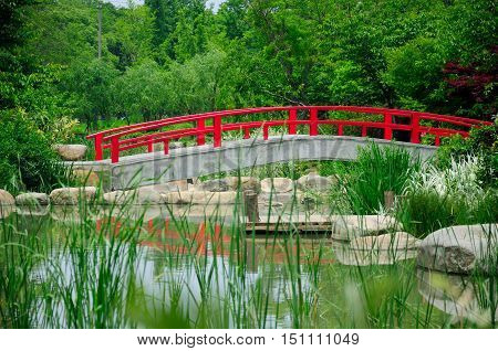 An arched cement bridge with red railings over a small pond within the Taihu or Lake Tai scenic area in Wuxi China in Jiangsu province.