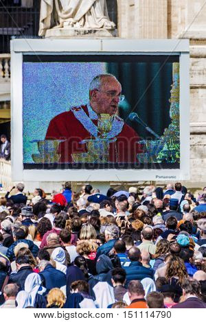 Rome 13 April 2014: A group of believers in St. Peter's Square on Palm Sunday during the Eucharistic blessing of Pope Francis. Pope Francis on the big screen. April 23 2014 Vatican City Italy